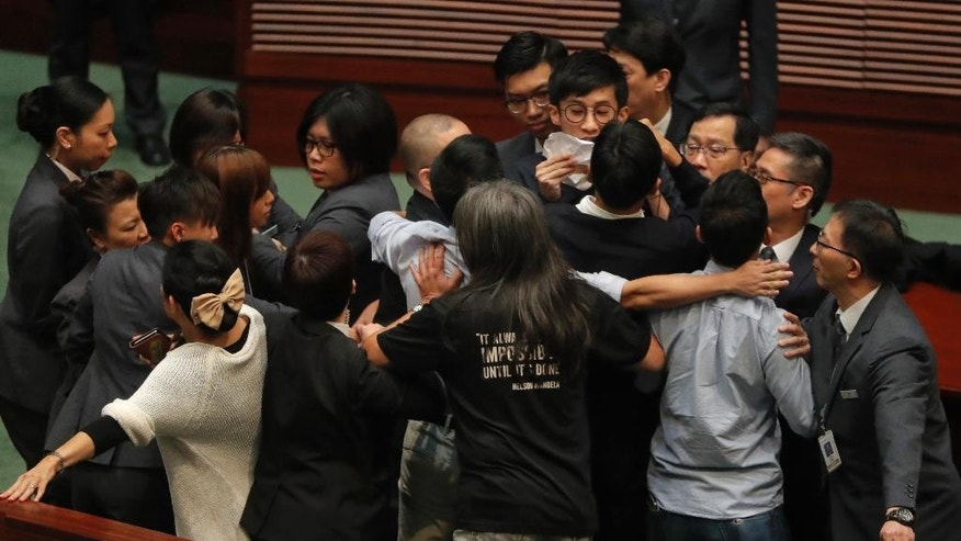 Newly elected Hong Kong lawmaker Sixtus Leung, upper center with glasses and holding paper, is blocked by security guards in gray suits, after he tries to retake the oath at the legislature council in Hong Kong, Wednesday, Nov. 2, 2016. Two newly elected pro-democracy Hong Kong lawmakers barred for insulting China in their swearing-in ceremony have set off another round of disorder by scuffling with guards as they tried to retake their oaths in the chamber. (AP Photo/Vincent Yu)