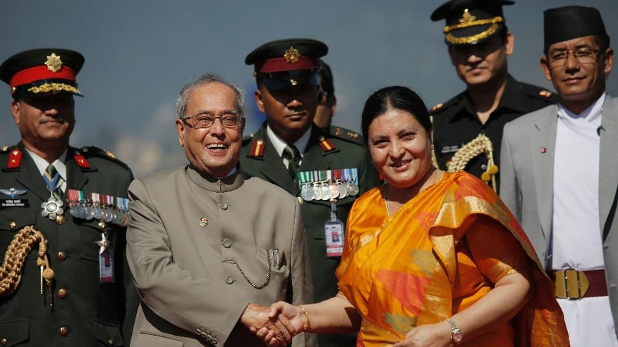 Nepalese President Bidhya Devi Bhandari, center right, shakes hand with Indian President Pranab Mukherjee on his arrival at the Tribhuwan international Airport in Kathmandu, Nepal, Wednesday, Nov. 2, 2016. Mukherjee flew to Nepal Wednesday for a three-day visit that is mostly a goodwill and pilgrimage trip to the Himalayan nation. (AP Photo/Niranjan Shrestha)