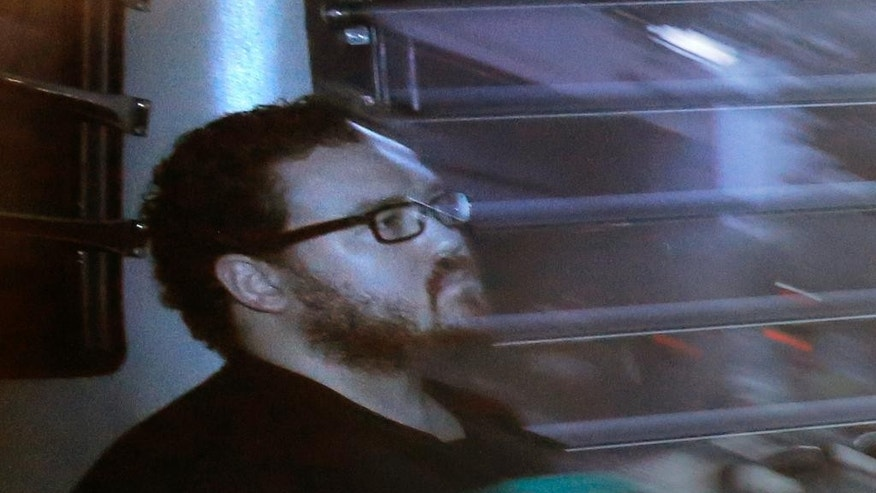 FILE - In this Nov. 24, 2014, file photo taken through tinted glass, Rurik Jutting, a British banker, sits in a prison bus as he arrives at a court in Hong Kong. The Hong Kong trial of British stock trader Jutting who murdered two Indonesian women and horrifically tortured one of them, recording the three-day ordeal on his phone, has barely registered in the victims' home country, let alone elicited shock or sympathy. (AP Photo/Vincent Yu, File)