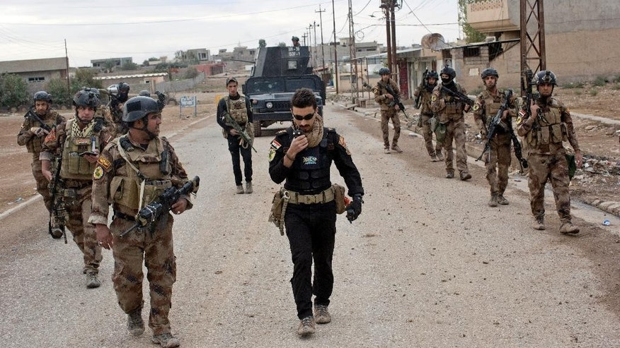 Iraqi special forces soldiers patrol a street in Gogjali, an eastern district of Mosul, Iraq, Wednesday, Nov. 2, 2016. Iraqi special forces paused their advance in the eastern district of Mosul on Wednesday to clear a neighborhood of any remaining Islamic State militants, killing at least eight while carrying out house-to-house searches. (AP Photo/Marko Drobnjakovic)