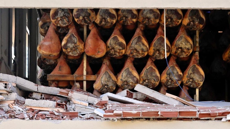 In this photo taken on Monday Oct. 31, 2016 cured hams hang in a damaged plant in Norcia, Italy. The earthquake in Italy this week has hit the local region's economy where it hurts. The makers of prized hams and dairy businesses have seen their plants torn up and are struggling to sell stock before it spoils. The tourism sector is all but dead for the foreseeable future (AP Photo/Gregorio Borgia)