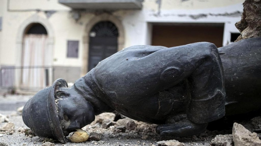 The monument of the Unknown Soldier lies on the ground after falling, in San Pellegrino, near Norcia, central Italy, Wednesday, Nov. 2, 2016. Authorities say more than 100,000 people were affected by the 6.6-magnitude quake on Sunday, either sustaining property damage or being frightened from their homes as the quakes hit the same region reeling from a deadly quake in August. (Massimo Percossi/ANSA via AP)