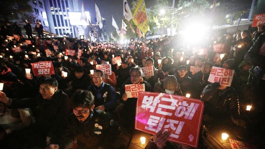 "Protesters stage a rally, calling for South Korean President Park Geun-hye to step down in downtown Seoul, South Korea, Wednesday, Nov. 2, 2016. South Korean prosecutors requested an arrest warrant for a longtime friend of Park on Wednesday over allegations of influence-peddling and other activities that have triggered a huge political scandal that threatens Park's leadership. Placards read: ""Park Geun-hye should step down."" (AP Photo/Ahn Young-joon)"