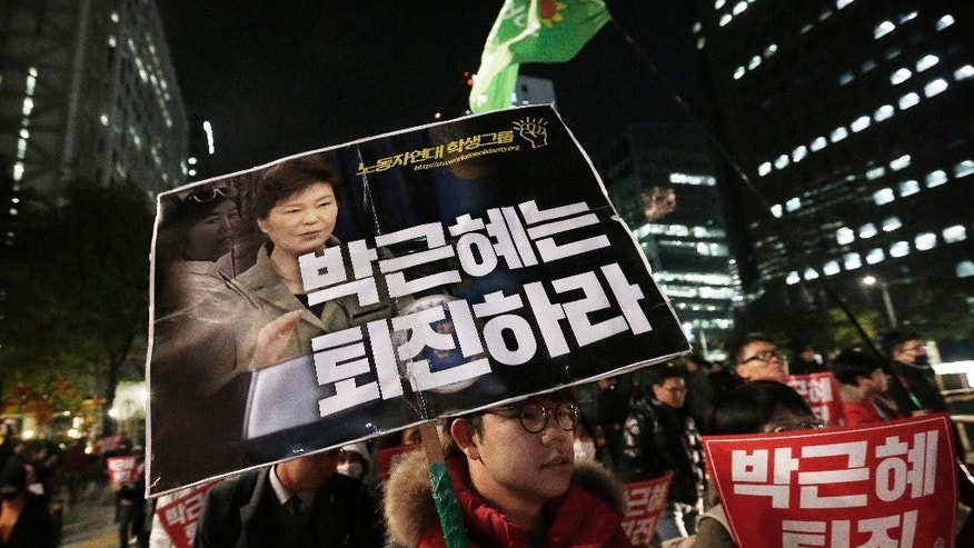 "A South Korean protester carries a placard showing images of South Korean President Park Geun-hye and Choi Soon-sil, top left, who is at the center of a political scandal, during a rally, calling for Park to step down in downtown Seoul, South Korea, Wednesday, Nov. 2, 2016. South Korean prosecutors requested an arrest warrant for the longtime friend of Park on Wednesday over allegations of influence-peddling and other activities that have triggered a huge political scandal that threatens Park's leadership. The placard reads: ""Park Geun-hye should step down."" (AP Photo/Ahn Young-joon)"