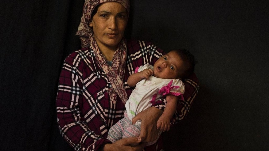In this Tuesday Sept. 13, 2016 photo 33-year-old Kaouser Tamo, a Syrian mother from Al Hasakah, poses with her baby girl Shidra Abdul Gani Ahmed in a tent made of blankets given by the UNCHR at the Ritsona refugee camp in Greece. Kaouser is one of the hundreds of refugee women who gave birth while stranded in Greece. Shidra, the family's sixth child, was born on Sunday, July 16, 2016 in an Athens hospital. (AP Photo/Petros Giannakouris)