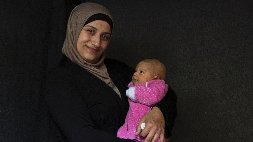 In this Wednesday Oct.12, 2016 photo 28-year-old Hala Baroud, a Syrian mother from Latakia, poses with her baby girl Farah in a tent made of blankets given by the UNCHR at the Ritsona refugee camp in Greece. Hala is one of the dozens of refugee women who gave birth while stranded in Greece. Farah, the family's second child, was born on Wednesday Aug, 31, 2016 in an Athens hospital.  (AP Photo/Petros Giannakouris)