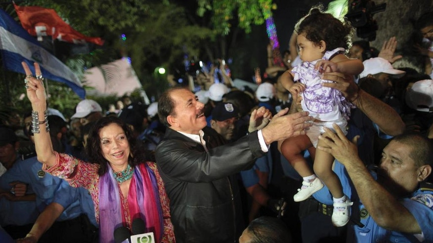 FILE.- In this Nov. 8, 2011 file photo Nicaragua's President Daniel Ortega, center, accompanied by his wife Rosario Murillo, left, greets supporters after delivering an address to the nation in Revolution Square in Managua, Nicaragua. First lady Rosario Murillo has increasingly become the public face of Nicaragua's government and many say she wields more power than anyone in the country save Ortega himself. Now running as his VP ticket mate in a Nov. 6 election seen as a shoo-in, Murillo is poised to finally have the title to match her true influence.(AP Photo/Esteban Felix, File)