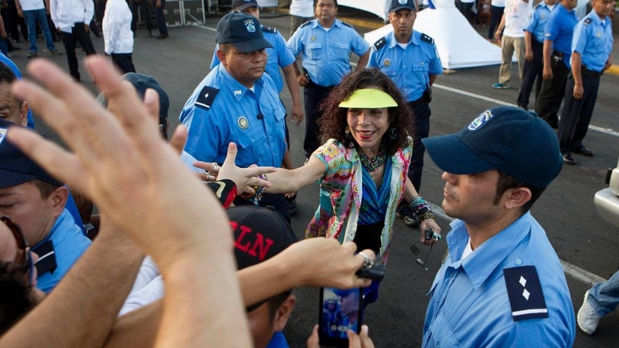 FILE - In this June 20, 2014 file photo, Nicaragua's first lady Rosario Murillo greets supporters during the commemoration of the 35th anniversary of the Sandinista National Liberation Front, FSLN, withdrawal to Masaya, a tactical move by the FSLN that was critical in the overthrow of Anastasio Somoza's dictatorship, in Managua, Nicaragua. Murillo has taken on ever greater responsibility during the last decade that her husband has been in office. She is said to run Cabinet meetings and many Nicaraguans credit her for social programs that have helped keep the ruling Sandinista party's popularity ratings high. (AP Photo/Esteban Felix, File)