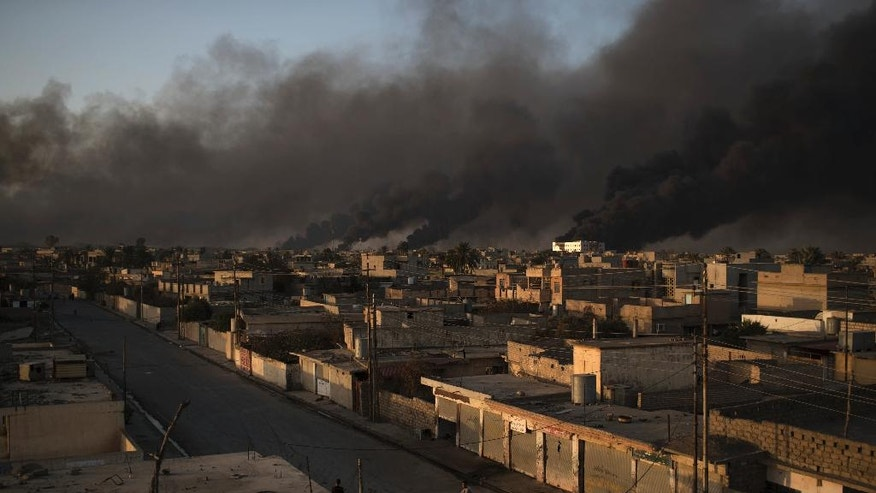 FILE - In this Monday, Oct. 31, 2016 file photo, a man rides his bike on a street as smoke rises from burning oil fields in Qayara, some 50 kilometers south of Mosul, Iraq. The operation that pushed Islamic State militants out of Shura _ a small village some 35 kilometers south of Mosul, made up of no more than 1,000 houses _ required days of preparation and some two thousand Iraqi troops to take on no more than 50 IS fighters. That's indicative of Iraq's overall military strategy on Mosul's southern approach, where dozens of villages with civilian populations have repeatedly slowed ground forces. (AP Photo/Felipe Dana, File)