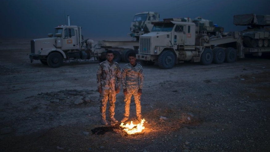 FILE - In this Tuesday, Nov. 1, 2016 file photo, Iraqi army soldiers warm themselves next to a fire near the Qayara air base, south of Mosul, Iraq. The operation that pushed Islamic State militants out of Shura _ a small village some 35 kilometers south of Mosul, made up of no more than 1,000 houses _ required days of preparation and some two thousand Iraqi troops to take on no more than 50 IS fighters. That's indicative of Iraq's overall military strategy on Mosul's southern approach, where dozens of villages with civilian populations have repeatedly slowed ground forces. (AP Photo/Felipe Dana, File)