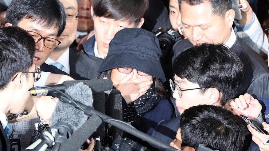 In this Monday, Oct. 31, 2016 photo, Choi Soon-sil, center, who is at the center of a political scandal, is surrounded by media upon her arrival at the Seoul Central District Prosecutors' Office in Seoul, South Korea. South Korean prosecutors requested an arrest warrant Wednesday, Nov. 2, for the longtime friend of President Park Geun-hye over allegations of influence-peddling and other activities that have triggered a huge political scandal that threatens Park's leadership. (AP Photo/Lee Jin-man)