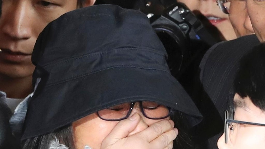 FILE - In this Oct. 31, 2016, file photo, Choi Soon-sil who is at the center of a political scandal, is surrounded by media upon her arrival at the Seoul Central District Prosecutors' Office in Seoul, South Korea. South Korean prosecutors requested an arrest warrant Wednesday, Nov. 2, for the longtime friend of President Park Geun-hye over allegations of influence-peddling and other activities that have triggered a huge political scandal that threatens Park's leadership. (AP Photo/Lee Jin-man, File)