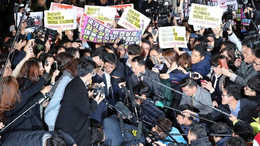 In this Monday, Oct. 31, 2016 photo, Choi Soon-sil, center, who is at the center of a political scandal, is surrounded by media, prosecutors' officers and protesters upon her arrival at the Seoul Central District Prosecutors' Office in Seoul, South Korea. South Korean prosecutors requested an arrest warrant Wednesday, Nov. 2, for the longtime friend of President Park Geun-hye over allegations of influence-peddling and other activities that have triggered a huge political scandal that threatens Park's leadership. (AP Photo/Lee Jin-man)