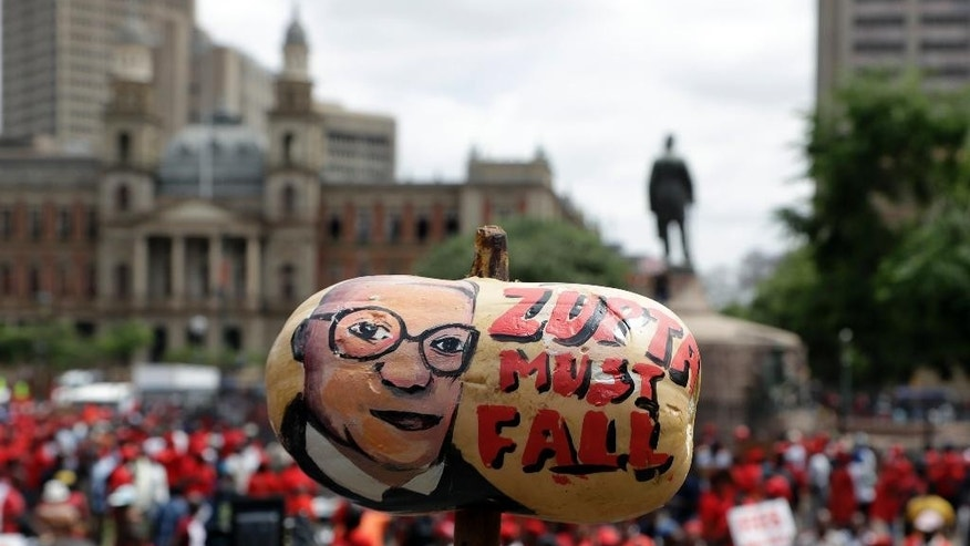 A protester holds a butternut squash painted with an image of South African President Jacob Zuma, during an anti-government march outside a court in Pretoria, South Africa, Wednesday, Nov. 2, 2016. Thousands of South Africans are demonstrating for the resignation of President Jacob Zuma, who has been enmeshed in scandals that critics say are undermining the country's democracy. (AP Photo/Themba Hadebe)