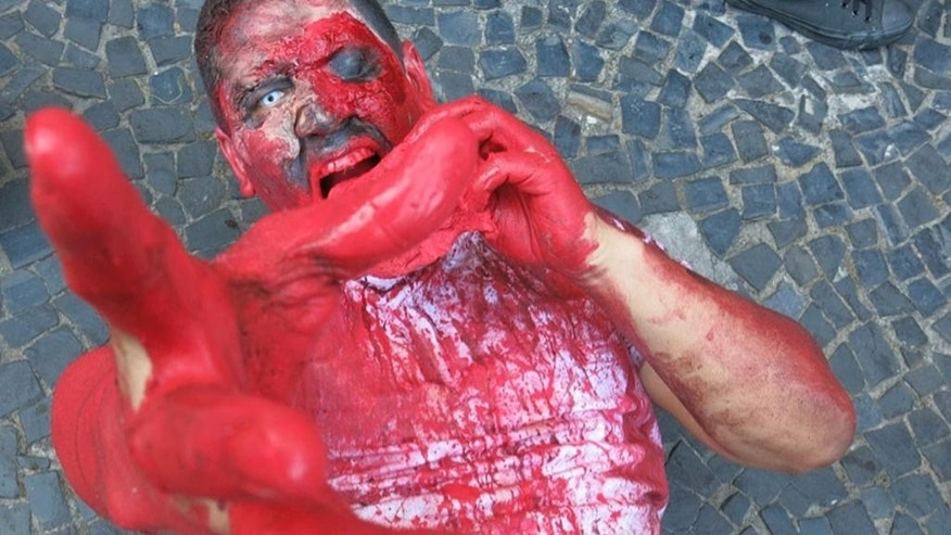 "Marcelo Alves, a 28-year-old resident of Rio de Janeiro, pretends to eat flesh and grab at onlookers while participating in a ""Zombie Walk"" along Copacabana Beach, Wednesday, Nov. 2, 2016. Hundreds of Rio residents participated in the event, one of many planned throughout the country. Such zombie celebrations have become popular worldwide in recent years thanks to the popular AMC television series ""The Walking Dead."" (AP Photo/Peter Prengaman)"