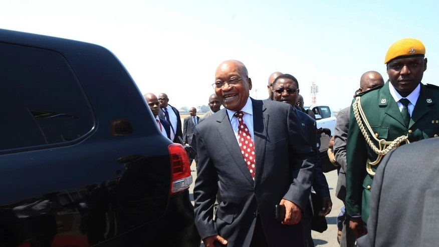South African President Jacob Zuma smiles upon arrival in Harare, Zimbabwe, Thursday, Nov, 3, 2016. Zuma has travelled to neighboring Zimbabwe on state business following the release of a state watchdog report indicating possible South African government corruption linked to him and his associates. (AP Photo/Tsvangirayi Mukwazhi)
