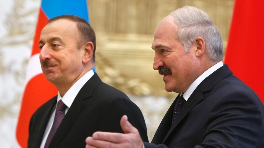 FILE In this Saturday, Nov. 28, 2015 file photo Belarusian President Alexander Lukashenko, right, welcomes Azerbaijan President Ilham Aliyev, left, in Minsk, Belarus. Mired in a multi-year recession and bitter loan talks with the International Monetary Fund, it would appear a strange time for Belarus to take on the burden of hosting a major sports event, the 2019 European Games. (AP Photo/Sergei Grits, File)