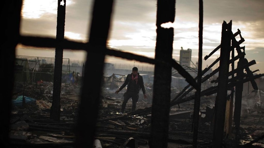 A migrant looks at the remains of a shop burnt in the makeshift migrant camp near Calais, northern France, Wednesday, Oct. 26, 2016. Firefighters have doused several dozen fires set by migrants as they left the makeshift camp where they have been living near the northern French city of Calais. (AP Photo/Emilio Morenatti)