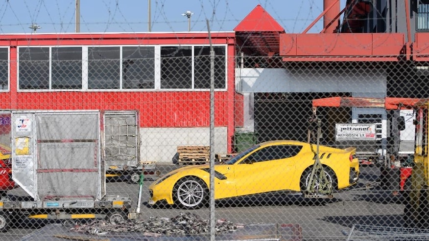 A Ferrari sports car is  being towed off the freight zone by the police at Geneva Airport, in Geneva, Switzerland, on Thursday, Nov.3  2016. Geneva authorities have confiscated 11 luxury vehicles and sports cars Monday  belonging to Teodorin Obiang Nguema,, the son of Equatorial Guinea's president as part of a preliminary investigation into alleged corruption.  (Laurent Gillieron/Keystone via AP)