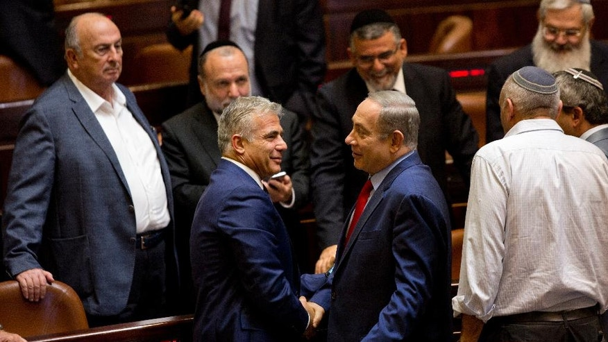 In this Monday, Oct. 31, 2016 photo, Israeli Prime Minister Benjamin Netanyahu, center right, shakes hands with Yair Lapid, leader of the Yesh Atid party, during a session at the Knesset, Israel's parliament, in Jerusalem. Lapid believes he has finally found a formula that will allow him to do something that has eluded Israeli politicians for nearly a decade: Defeat Prime Minister Benjamin Netanyahu in an election. Just three years after Lapid gave up a successful media career for the rough-and-tumble of Israeli politics, his centrist Yesh Atid party has been surging in opinion polls -- repeatedly coming out ahead of Netanyahu's long-dominant Likud Party. (AP Photo/Sebastian Scheiner)