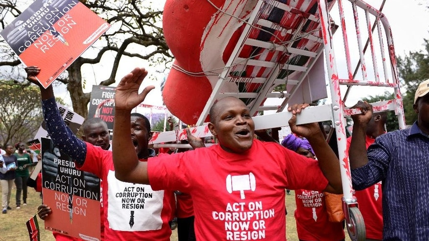 Demonstrators carry a mock hospital bed covered in fake blood to illustrate the slogan that Kenyans are bleeding due to poor hospital services caused by corruption, in Nairobi, Kenya Thursday, Nov. 3, 2016. Police in Kenya's capital fired tear gas on protesters demanding that the president act on rampant corruption or resign, following allegations which the government denies that around $50 million has been diverted from the health ministry. (AP Photo)