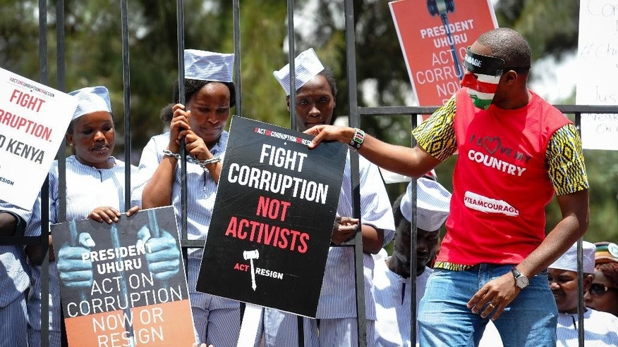 Demonstrators wear mock prison outfits to show that they want to imprison those engaged in corruption, in Nairobi, Kenya Thursday, Nov. 3, 2016. Police in Kenya's capital fired tear gas on protesters demanding that the president act on rampant corruption or resign, following allegations which the government denies that around $50 million has been diverted from the health ministry. (AP Photo)
