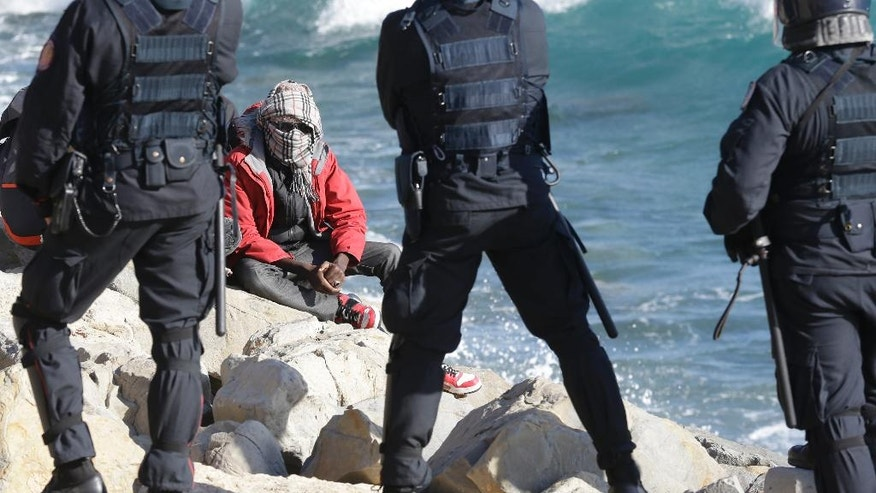 FILE - This Sept. 30, 2015 photo shows a migrant facing Italian police officers in riot gear after the evacuation of a tent camp at the Franco-Italian border in Ventimiglia, Italy. In a report by human rights watchdog Amnesty International published Thursday, Nov. 3, 2016, the organization alleges that Italian police have beaten and abused migrants and unlawfully expelled some, under pressure to implement new European Union rules to process arrivals.  (AP Photo/Lionel Cironneau, files)