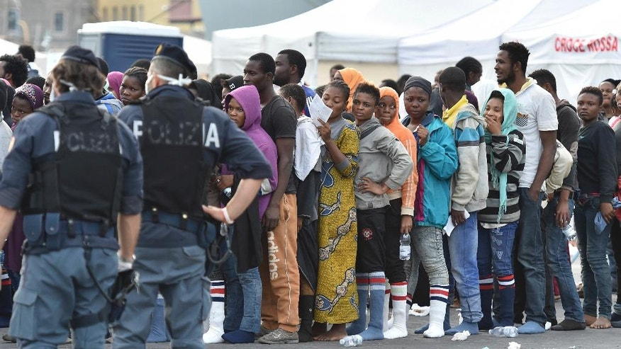 FILE - In this June 8, 2015 file photo, police monitor rescued migrants standing in a line after they were disembarked from the British Royal Navy ship HMS Bulwark at Catania harbor, Italy. In a report by human rights watchdog Amnesty International published Thursday, Nov. 3, 2016, the organization alleges that Italian police have beaten and abused migrants and unlawfully expelled some, under pressure to implement new European Union rules to process arrivals.  (AP Photo/Carmelo Imbesi, files)
