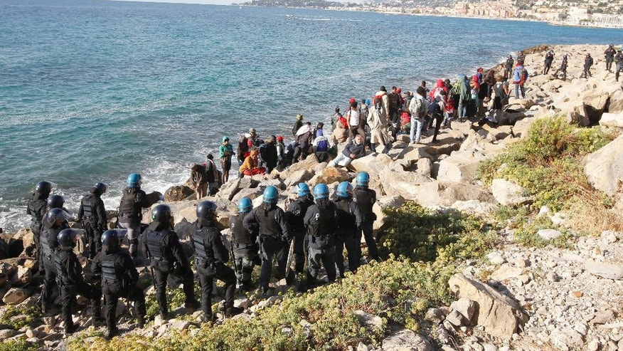 FILE - This Sept. 30, 2015 photo shows migrants facing Italian police officers in riot gear after the evacuation of a tent camp at the Franco-Italian border in Ventimiglia, Italy. In a report by human rights watchdog Amnesty International published Thursday, Nov. 3, 2016, the organization alleges that Italian police have beaten and abused migrants and unlawfully expelled some, under pressure to implement new European Union rules to process arrivals.  (AP Photo/Lionel Cironneau, files)