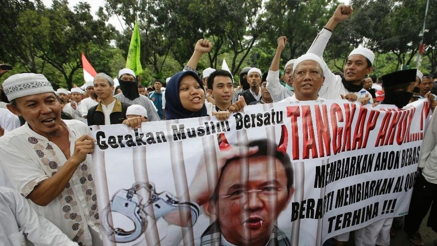 "In this Friday, Oct. 14, 2016, photo, Muslim protesters hold a banner calling for the arrest of Jakarta's ethnic Chinese and Christian Governor Basuki Tjahaja Purnama, popularly known as ""Ahok"", outside the City Hall. Indonesian police are planning a massive show of force in the capital Jakarta on Friday to contain a much-hyped protest by Muslim hardliners against the city's popular governor that threatens to ignite the country's religious and racial flashpoints. (AP Photo/Achmad Ibrahim)"