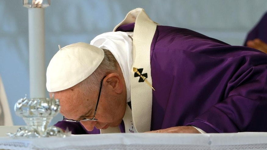 Pope Francis kisses the altar as he celebrates a Mass on the occasion of All Souls' Day, at the Prima Porta Cemetery in Rome, Wednesday, Nov. 2, 2016. (AP Photo/Gregorio Borgia)