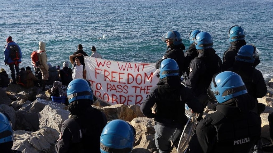FILE - This Sept. 30, 2015 photo shows migrants facing Italian police officers in riot gear at the Franco-Italian border in Ventimiglia, Italy. In a report by human rights watchdog Amnesty International published Thursday, Nov. 3, 2016, the organization alleges that Italian police have beaten and abused migrants and unlawfully expelled some, under pressure to implement new European Union rules to process arrivals.  (AP Photo/Lionel Cironneau, files)