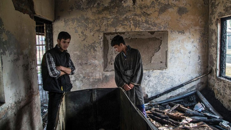 "FILE - In this Tuesday, Nov. 1, 2016 file photo, Kashmiri Muslim student Hilal Ahmed Hajam, left, and Nasir Ahmed Mir inspect the damage of a partially burned government high school in Goripora, on the outskirts of Srinagar, India controlled Kashmir. Many schools in the disputed Himalayan region are already shut since July amid months of anti-India protests and street clashes that have left at least 90 dead. Nearly 26 school buildings have been torched by people police describe as ""miscreants,"" without naming any arson suspects. (AP Photo/Dar Yasin, File)"