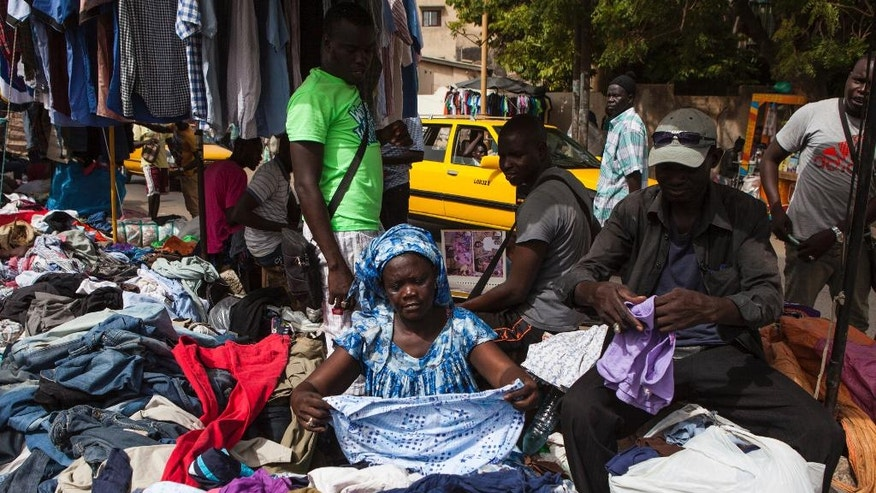 In this photo taken Thursday, Oct. 20, 2016, vendor Mourianne Gnagna Cisse, center, sorts through her stock of clothing at the second hand clothes market in Colobane neighborhood in Dakar, Senegal. Secondhand T-shirts, jeans and dresses are piled high for blocks along the busy streets in the neighborhood, where people buy donated European and American fashions at a fraction of their original price. (AP Photo/Jane Hahn)