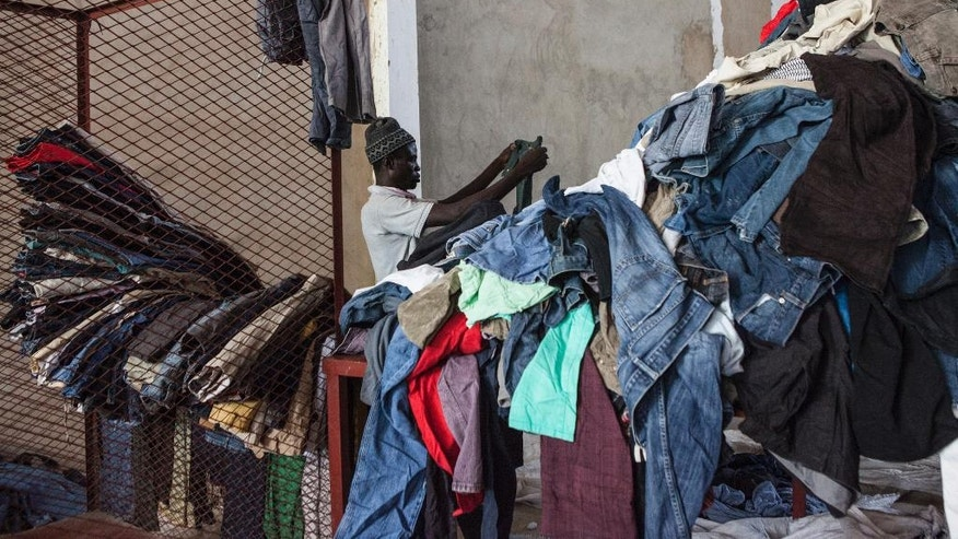 In this photo taken Monday, Oct. 24, 2016, Dame Sall, sorts and folds secondhand jeans imported from Italy at the the Invotex warehouse in Dakar, Senegal. Secondhand T-shirts, jeans and dresses are piled high for blocks along the busy streets in Dakar's Colobane neighborhood, where people buy donated European and American fashions at a fraction of their original price. (AP Photo/Jane Hahn)