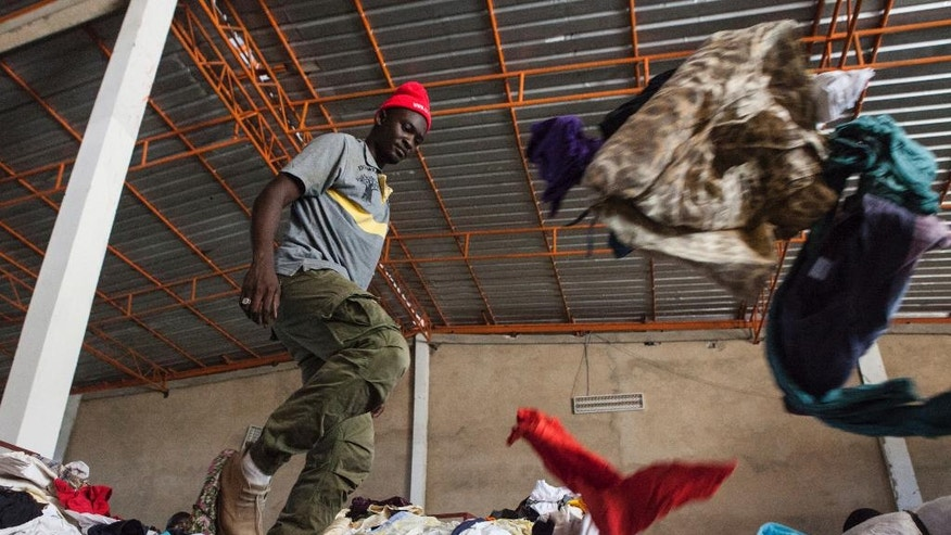 In this photo taken Monday, Oct. 24, 2016, Lamine Mbow, and other workers sort through secondhand clothing imported from Italy at the the Invotex warehouse in Dakar, Senegal. Secondhand T-shirts, jeans and dresses are piled high for blocks along the busy streets in Dakar's Colobane neighborhood, where people buy donated European and American fashions at a fraction of their original price. (AP Photo/Jane Hahn)