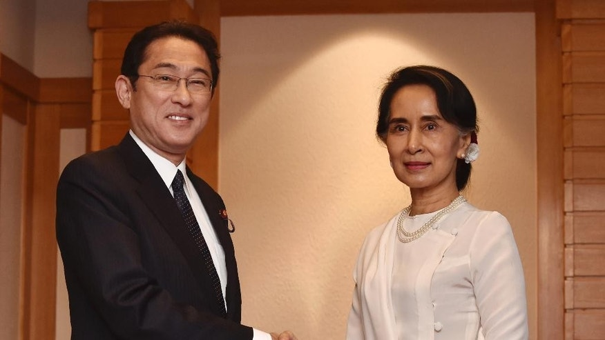 Myanmar State Counsellor and Foreign Minister Aung San Suu Kyi, right,  shakes hands with Japan's Foreign Minister Fumio Kishida, left,  prior to their talks at a hotel in Tokyo Thursday, Nov. 3, 2016.  During her five-day visit, Suu Kyi is to meet with Japanese business leaders to seek investment. She also will travel to Kyoto to be awarded an honorary doctorate from Kyoto University, where she was a visiting scholar for one year. (Kazuhiro Nogi/Pool Photo via AP)