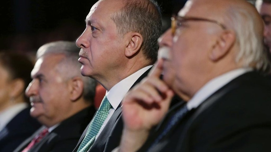 Turkey's President Recep Tayyip Erdogan, center, listens before addressing a meeting at his palace in Ankara, Turkey, Thursday, Nov. 3, 2016. Erdogan has harshly criticized Germany, accusing it of supporting terrorism and slamming comments suggesting Berlin may not extradite suspects wanted by Turkey if it considers the case is politically motivated.(Murat Cetinmuhurdar/Pool photo via AP)