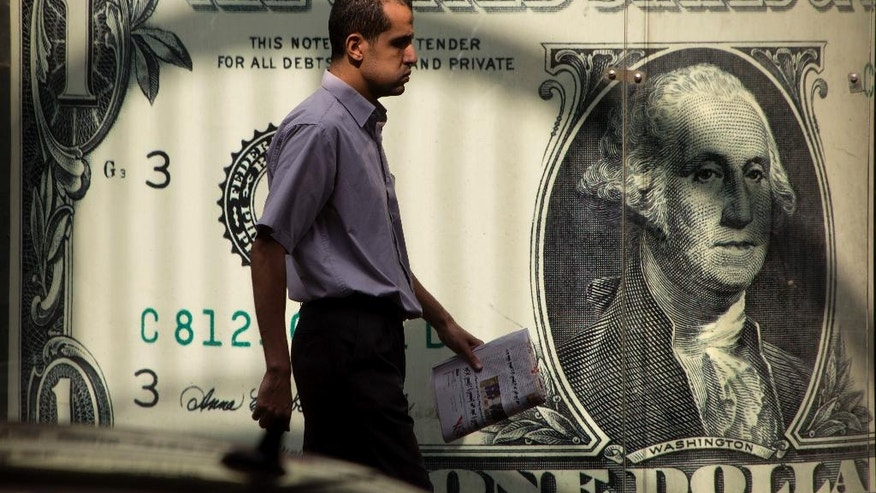 An Egyptian man walks past a poster showing a U.S. dollar outside an exchange office in Cairo, Egypt, Thursday, Nov. 3, 2016. Egypt has devalued its currency by 48 percent, meeting a key demand set by the International Monetary Fund in exchange for a $12 billion loan over three years to overhaul the country's ailing economy. The much heralded decision by the Egyptian Central Bank to devalue the pound followed a sharp and sudden decline this week in the value of the dollar in the unofficial market, plunging from an all-time high of 18.25 pounds to around 13 to the U.S. currency. (AP Photo/Amr Nabil)