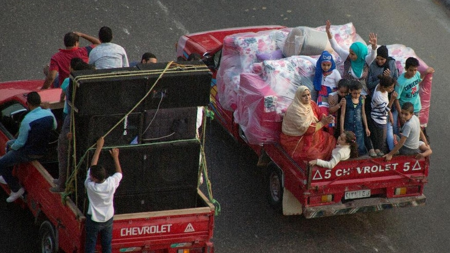 In this Friday, Oct. 28, 2016 photo, Egyptians ride in vehicles carrying a wedding furniture in Cairo. Egypt has devalued its currency by 48 percent, meeting a key demand set by the International Monetary Fund in exchange for a $12 billion loan over three years to overhaul the country's ailing economy. The much heralded decision by the Egyptian Central Bank to devalue the pound followed a sharp and sudden decline this week in the value of the dollar in the unofficial market, plunging from an all-time high of 18.25 pounds to around 13 to the U.S. currency. (AP Photo/Amr Nabil)