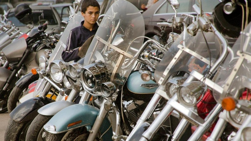 In this Friday, Oct. 28, 2016 photo, an Egyptian cleans Harley-Davidson motorbikes at a parking lot  in the upper class district of Zamalek, in Cairo. Egypt has devalued its currency by 48 percent, meeting a key demand set by the International Monetary Fund in exchange for a $12 billion loan over three years to overhaul the country's ailing economy. The much heralded decision by the Egyptian Central Bank to devalue the pound followed a sharp and sudden decline this week in the value of the dollar in the unofficial market, plunging from an all-time high of 18.25 pounds to around 13 to the U.S. currency. (AP Photo/Amr Nabil)