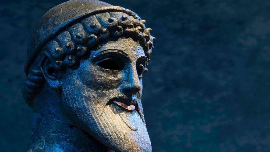 In this Tuesday, Oct. 4, 2016 photo, the 480 B.C. bronze statue of the ancient Greek god of the sea, Poseidon, is displayed at the National Archaeological Museum of Athens. Nearly 200 artefacts excavated all over the country are on show in the darkened temporary exhibition hall of the National Archaeological Museum in Athens, spotlit and blended with music, sounds of waves and creaking ship's blocks, and poetry. (AP Photo/Petros Giannakouris)