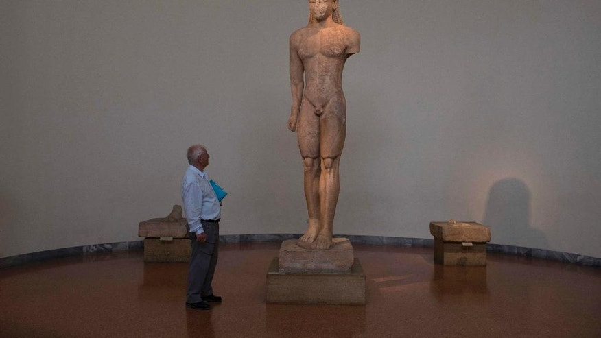 In this Wednesday, Oct. 5, 2016 photo, a visitor at the National Archaeological Museum of Athens looks at the 600 B.C. Naxian marble statue of a Kouros. The 3,05 meters height statue was found at the Temple of Poseidon at cape Sounion, near Athens. Nearly 200 artefacts excavated all over the country are on show in the darkened temporary exhibition hall of the National Archaeological Museum in Athens, spotlit and blended with music, sounds of waves and creaking ship's blocks, and poetry. (AP Photo/Petros Giannakouris)