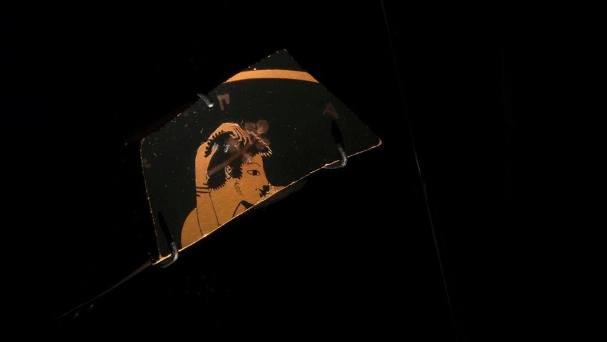 In this Tuesday, Oct. 4, 2016 photo, a potsherd from a red-figure kylix depicting a youth kissing a maiden is displayed at the National Archaeological Museum of Athens. The fragment dates from the 6th century BC and was found on the Acropolis.(AP Photo/Petros Giannakouris)