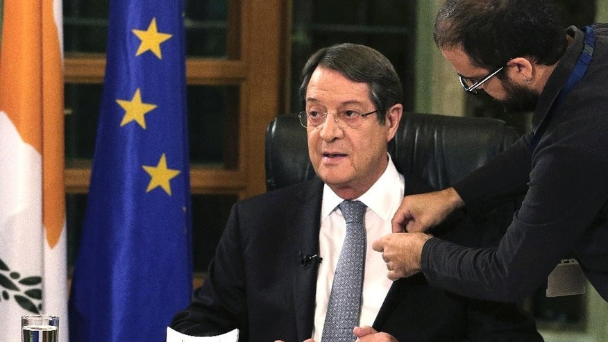 A television crew member adjusts a microphone on the jacket of Cyprus President Nicos Anastasiades before a nationally televised news conference at the Presidential Palace in Nicosia, Cyprus, Friday, Nov. 4, 2016. The president of ethnically divided Cyprus says Turkey's input will be pivotal in overcoming key obstacles preventing a reunification deal. Nicos Anastasiades, a Greek Cypriot, says he and breakaway Turkish Cypriot leader Mustafa Akinci have made significant progress on numerous issues making an envisioned federation workable. (Yiannis Kourtoglou/Pool Photo via AP)