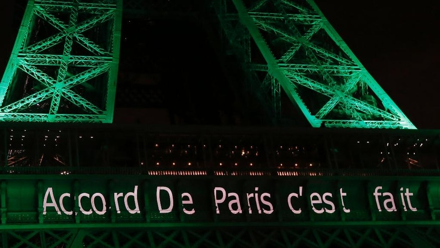 "The Eiffel Tower lit up in green to mark the success of the Paris Agreement, Friday Nov.4, 2016 in Paris. The Paris Agreement on climate change enters into force Friday faster than anyone had anticipated, after a year with remarkable success in international efforts to slash man-made emissions of carbon dioxide and other global warming gases. Inscription reads, ""Paris Agreement it's done"".(AP Photo/Michel Euler)"