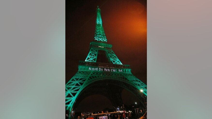 """The Eiffel Tower lit up in green to mark the success of the Paris Agreement, Friday Nov.4, 2016 in Paris. The Paris Agreement on climate change enters into force Friday faster than anyone had anticipated, after a year with remarkable success in international efforts to slash man-made emissions of carbon dioxide and other global warming gases. Inscription reads, """"it's done"""".(AP Photo/Michel Euler)"""