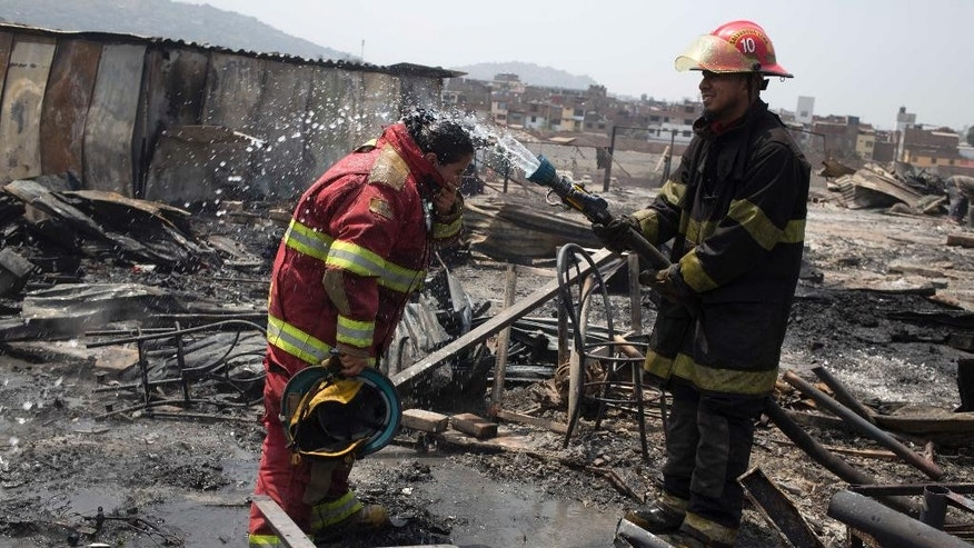 Firefighters cool off amid charred debris following an early morning fire that destroyed hundreds of homes, in the shantytown known as Cantagallo, in Lima, Peru, Friday, Nov. 4, 2016. The huge fire destroyed hundreds of homes where more than 3,000 members of Lima's Peruvian Amazon indigenous community have settled. It took firefighters more than six hours to get the fire under control, due to lack of water and difficult access to the area because of its narrow streets. No deaths have been reported. (AP Photo/Martin Mejia)