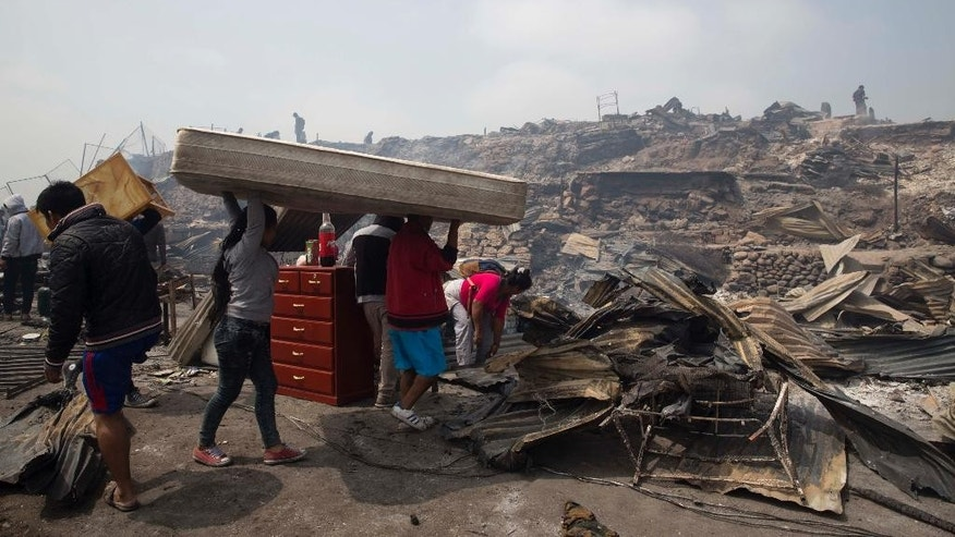 A family salvages a mattress from charred debris following an early morning fire that destroyed hundreds of homes, in the shantytown known as Cantagallo, in Lima, Peru, Friday, Nov. 4, 2016. The huge fire destroyed hundreds of homes where more than 3,000 members of Lima's Peruvian Amazon indigenous community have settled. It took firefighters more than six hours to get the fire under control, due to lack of water and difficult access to the area because of its narrow streets. No deaths have been reported. (AP Photo/Martin Mejia)