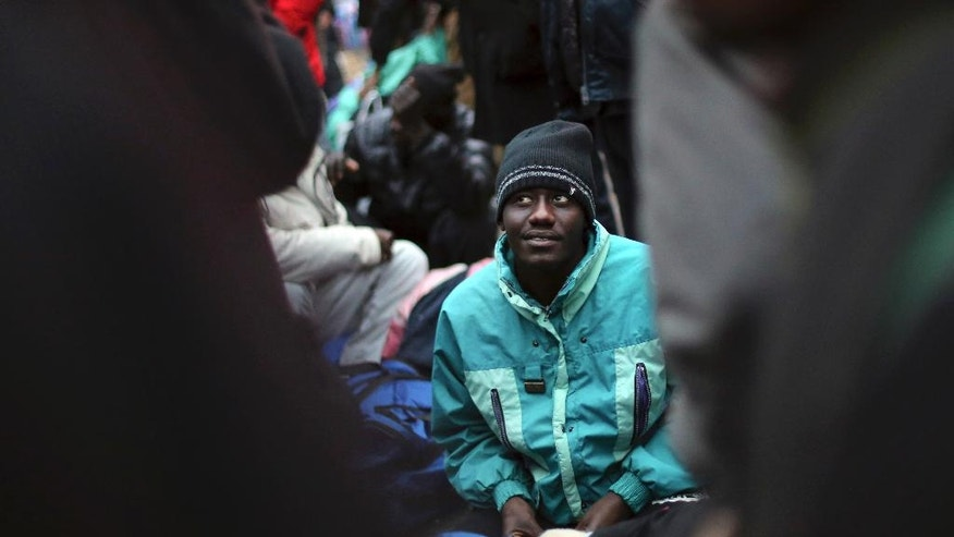 A migrant waits to board a bus to a temporary shelter in Paris, Friday, Nov. 4, 2016. Police and city officials are clearing out hundreds of migrants camped out on sidewalks in northern Paris in a camp that recently grew into a new challenge for the French government. (AP Photo/Thibault Camus)